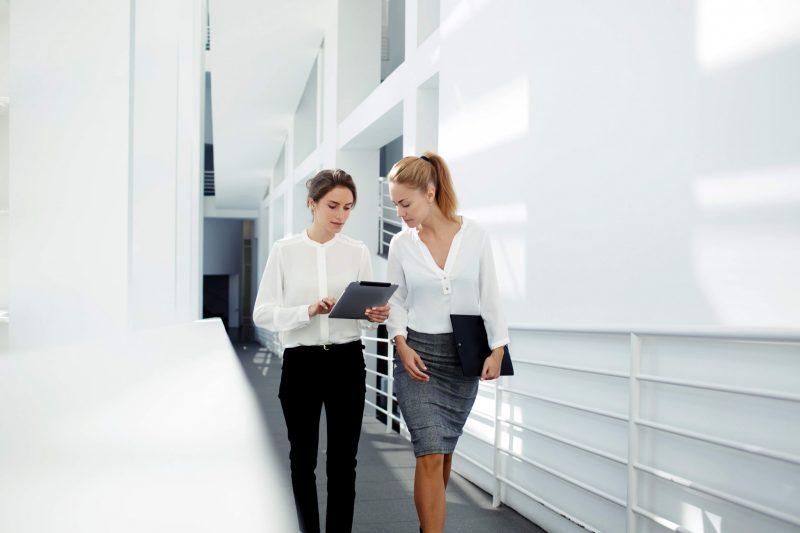 Två kvinnor som går och diskuterar något på en ipad