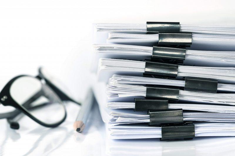 Glasögon papper och penna ligger på ett skrivbord