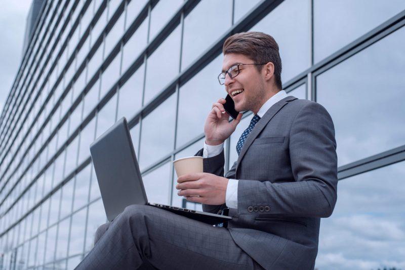 ung kiulle som dricker kaffe och tittar på datorn utomhus