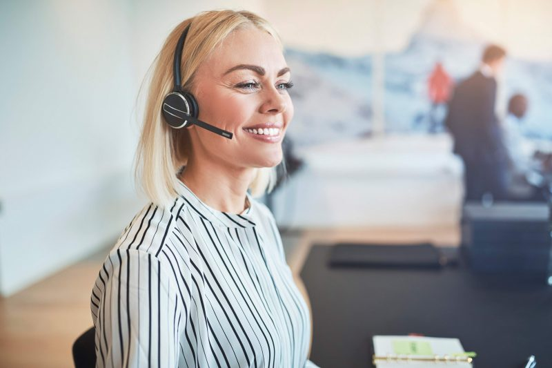 Glad kvinna pratar i telefon med headset
