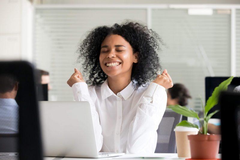 glad kvinna vid datorn