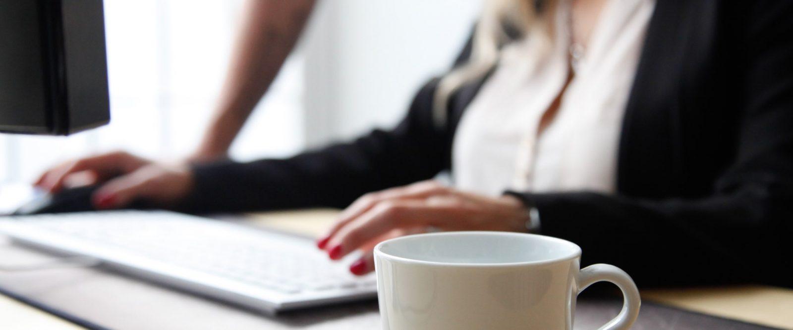 Kaffekopp som står framför person vid tangentbord