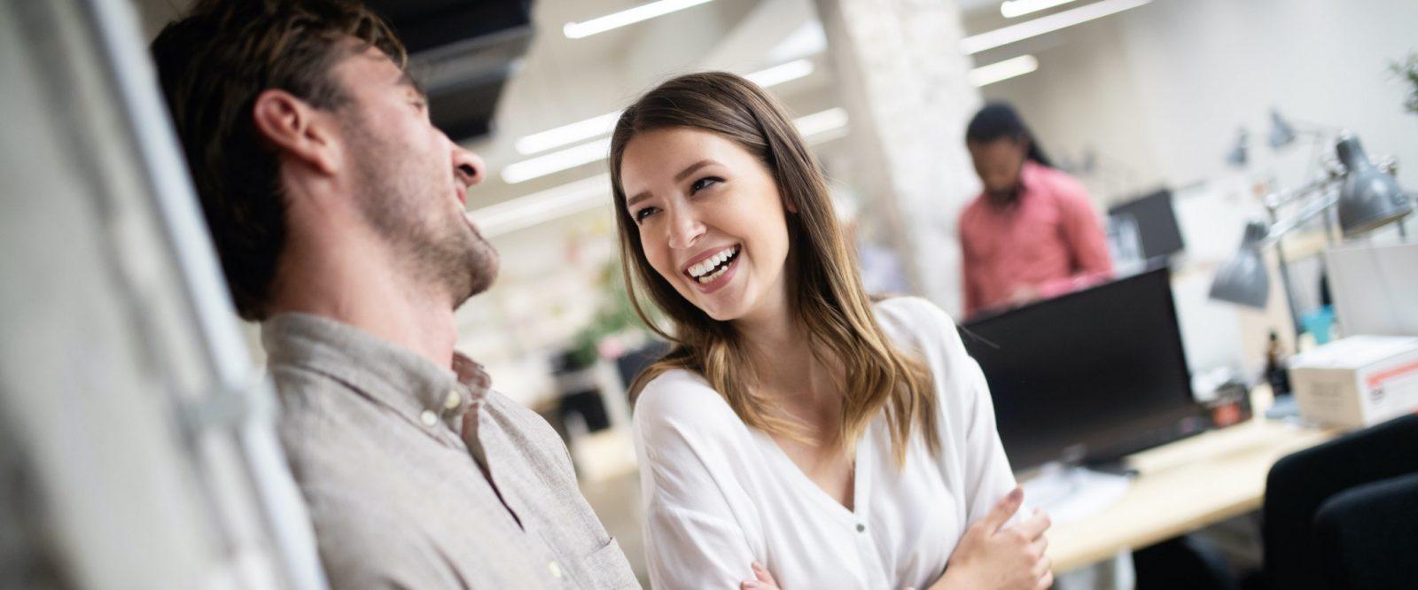 Två personer som skrattar och ler mot varandra