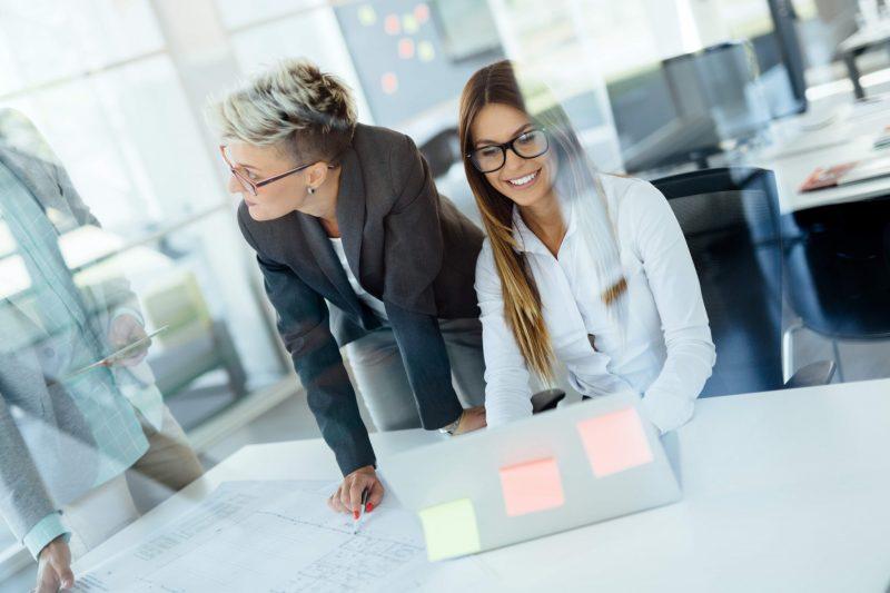Kollegor utför administrativt arbete i kontorsmiljö