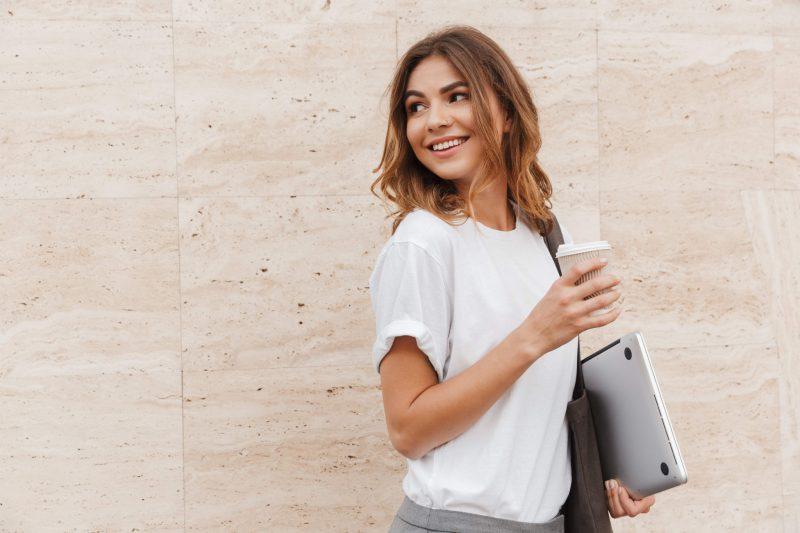 tjej med dator som tittar bakåt med en kaffe i handen