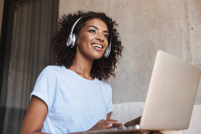 svart kvinna med lockigt hår som jobbar på datorn och lyssnar på något