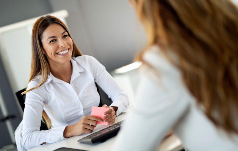 Två kvinnor pratar med varandra i ett möte