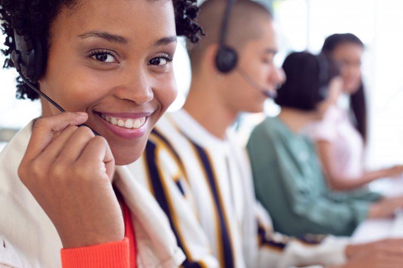 Kundtjänstmedarbetare med headset svarar på frågor från kunder